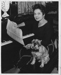 Revella Hughes at piano with dog by J. Foster
