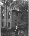 Jean Thomas in front of the Wee House in the Woods