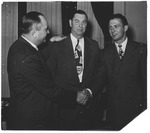 Cam Henderson shaking hands with Adolph Rupp, Andy Tonkovich on right