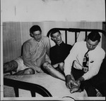 Cam Henderson treating ankle injury to Gene James, 1946-47