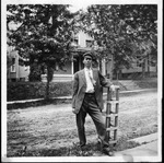 Cam Henderson standing by street, ca. 1910-1915