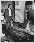 Frank Brumfield examining fire damage of apartment building, Huntington, 1960