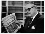 Huntington lawyer, Robert O. Ellis holding Huntington newspaper of Apr. 1, 1969
