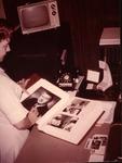 Dr. Carl Hoffman's head nurse, Annie Weber, working on his scrapbooks