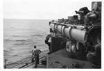 Torpedoman cleaning torpedo tubes after firing, USS Trathen, 1955