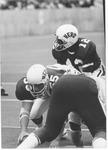 Center Dennis Foley (#55) centers ball to Bob Harris (#12),1970 MU Football team