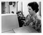 Pam Owens & Dr. George Arnold using video display terminal in newsroom