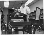 Charles Coffman, operating the lithographic press in MU Art Dept..