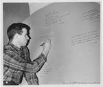 MU Junior Roger Drummond writing on
