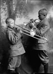 Two young African-American boys playing a trombone and a horn