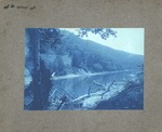 Unidentified location, woman seated on log by river